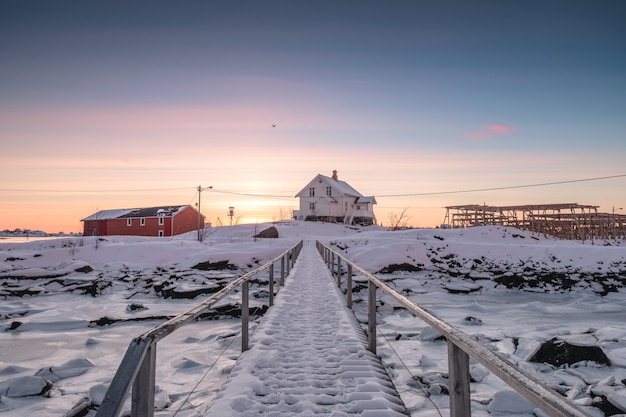 White house with wooden bridge and frozen coastline