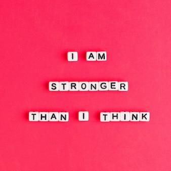 Bianco i am stronger than i think perline parole tipografia su rosso