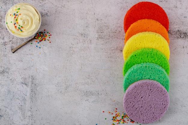 色の丸いスポンジケーキとボウルの白いアイシング。