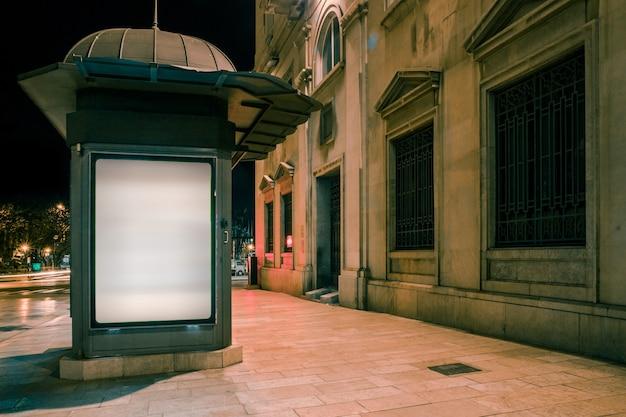 Tabellone per le affissioni in bianco illuminato bianco sul sentiero per pedoni alla notte