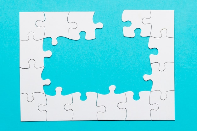 White incomplete white jigsaw puzzle over blue backdrop