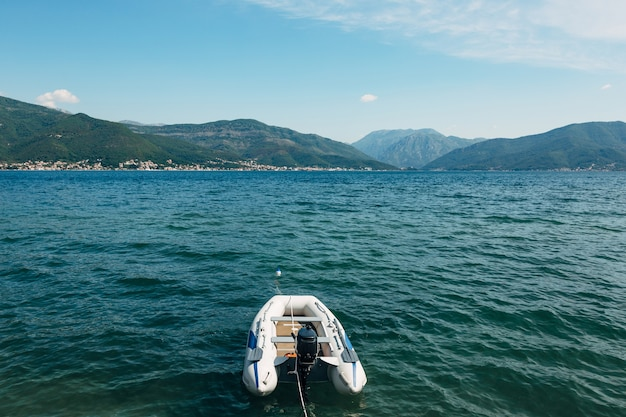 Белая надувная моторная лодка в которской бухте и зеленых горах