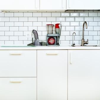 White interior design, modern and minimalist style kitchen with household appliances.