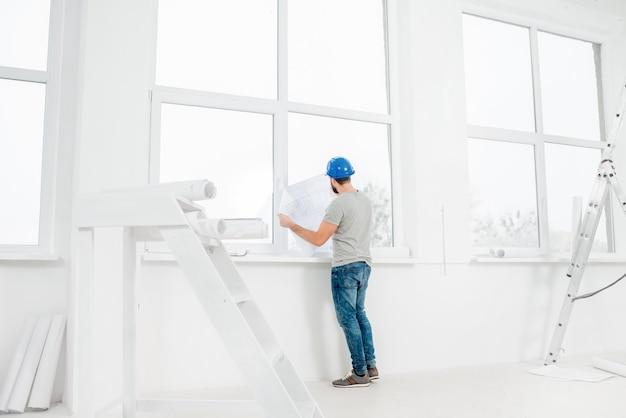 Белый интерьер для ремонта и ремонта с лестницей, окнами и прорабом или строителем, смотрящим на бумажные чертежи