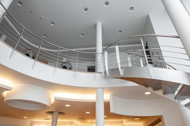 天井と曲がりくねった階段にスポットライトを当てたモダンな邸宅の白いインテリア