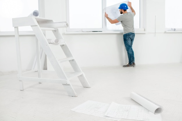 White interior for renovation and repair with ladder, windows and foreman or builder looking at paper drawings