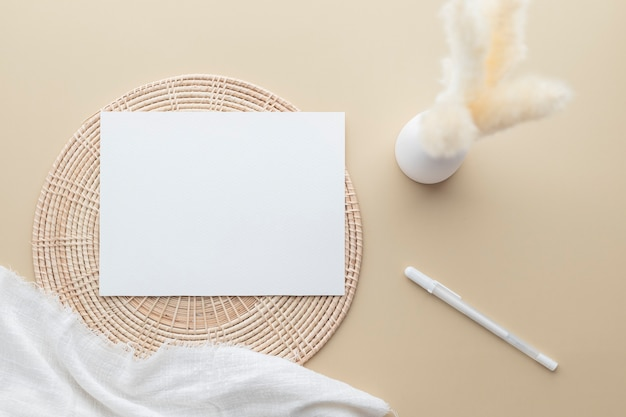 White invitation card, blank paper mockup on a beige background,  reeds grass in a vase, white blanket, rattan basket, flat lay, top view, copy space