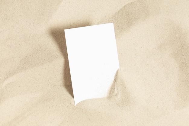 砂の上の白い招待カードのモックアップコンセプトビーチホリデーフラットレイ