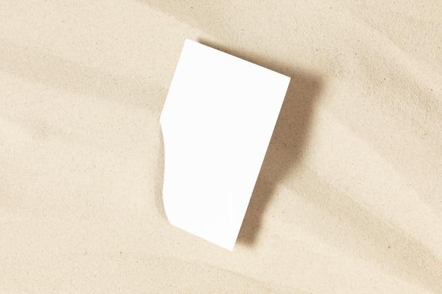 White invitation card mockup on sand concept beach holiday flat lay