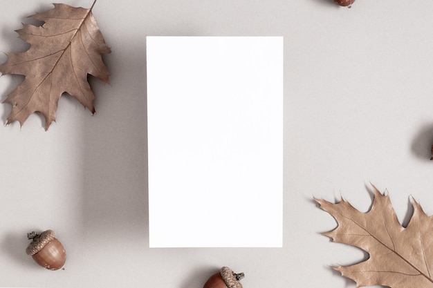 White invitation card mockup with autumn leaves on gray background flat lay top view copy space