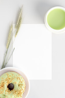 White invitation card mockup  with cup of green matcha tea an pistachio donut
