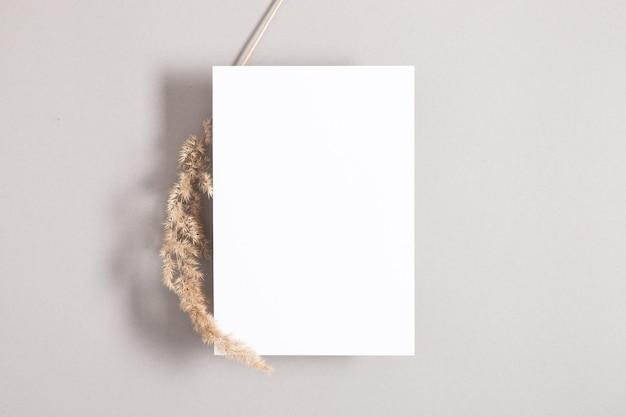 회색 배경에 마른 풀이 있는 흰색 초대 카드 흉내낸 평면 평면도 복사 공간