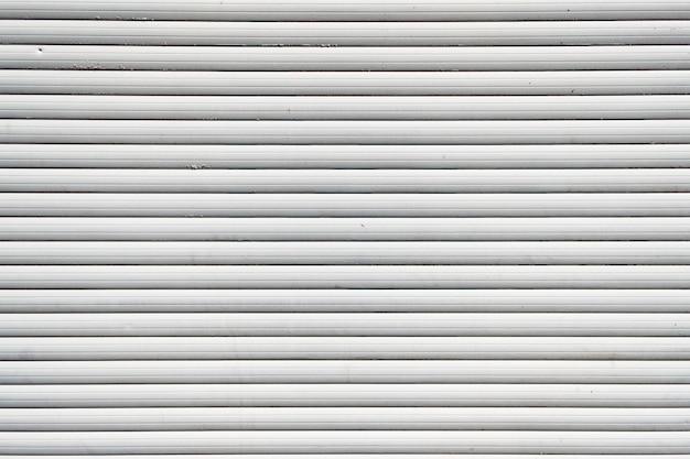 白い鉄のスズフェンスが並ぶ背景。金属の質感