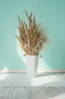 푸른 벽의 배경에 대해 팜파스 잔디의 마른 귀가있는 흰색 철제 꽃병 양동이