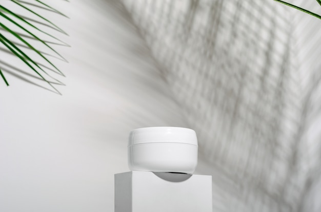 White jar of cream on a stand on a white with tropical palm leaves and their shadow.