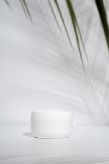 White jar of cream on a white with tropical palm leaves and their shadow.