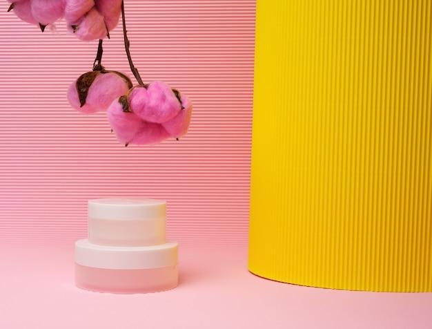 분홍색 배경에 화장품을 위한 흰색 항아리. 크림, 젤, 혈청, 광고 및 제품 판촉용 포장, 모형