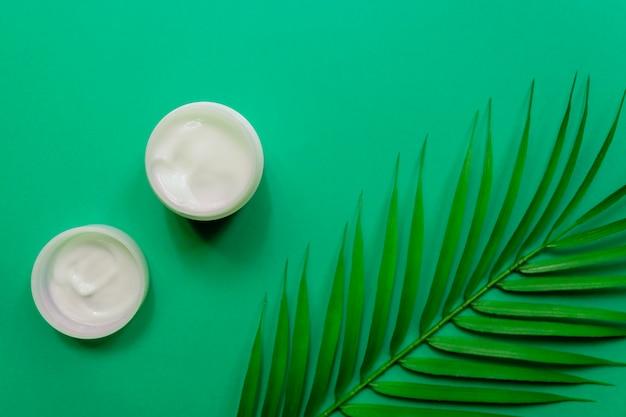 Белая банка крема для лица на фоне тропических пальмовых зеленых листьев. зеленый фон, вид сверху, плоская планировка. понятие о натуральной косметике.