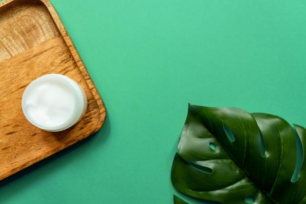 Белая банка крема для лица на деревянном подносе. зеленый фон, вид сверху, тропические листья. понятие о натуральной косметике и спа.