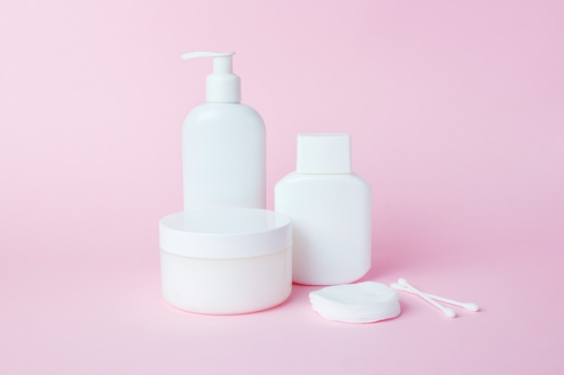 White jars of cosmetics on pink