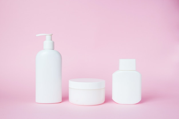 White jars of cosmetics on pink