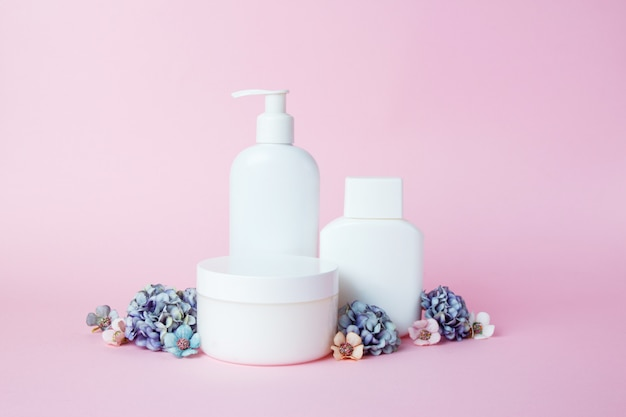 White jars of cosmetics with flowers on pink