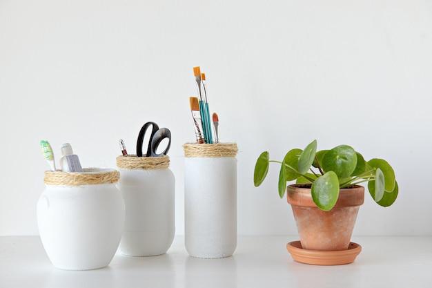 白い背景の最小限のスタイルでピレア植物で作られた白い瓶クラフト