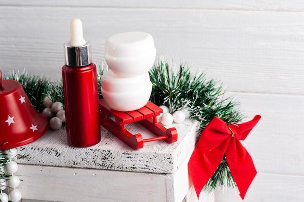 火のともったろうそくと赤いクリスマスの構成の白い瓶。美容製品のモックアップ