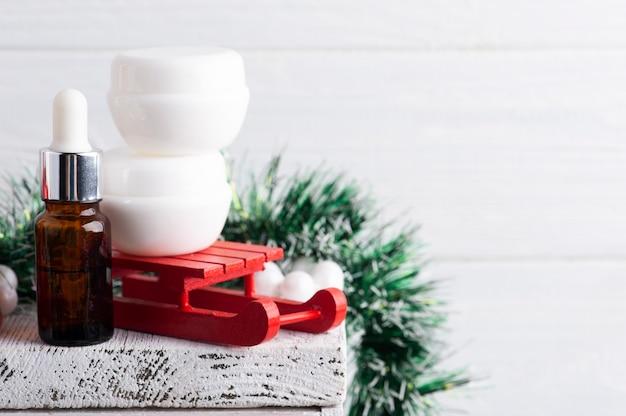 火のともったろうそくと赤いクリスマスの構成の白い瓶