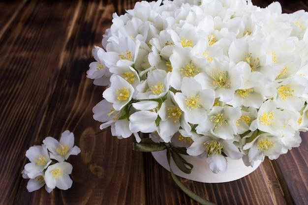 Белые цветы жасмина на деревянной доске