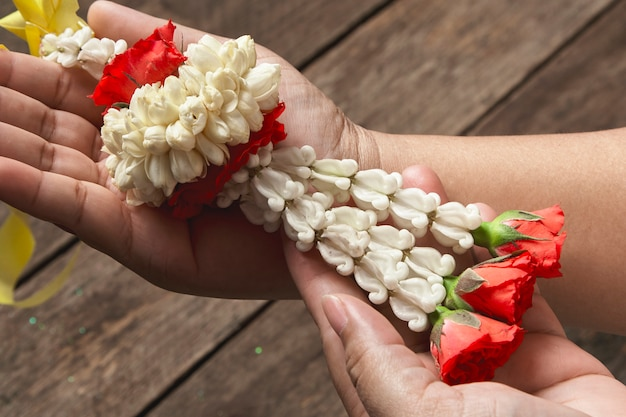 White jasmine garland on wood background, fresh thai style bouquet on the woman's hand