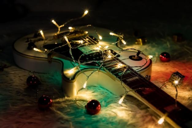어두운 배경에 흰색 재즈 기타와 크리스마스 장식. 어두운 배경에 불이 켜진 화환이 있는 일렉트릭 기타입니다. 크리스마스 또는 새해를 위한 선물 기타 클래식 모양.