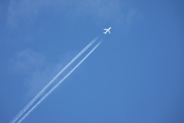 White jet airplane flying high in the blue sky
