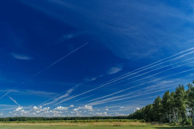 青い澄んだ雲ひとつない空を高高度で飛ぶ白いジェット旅客機