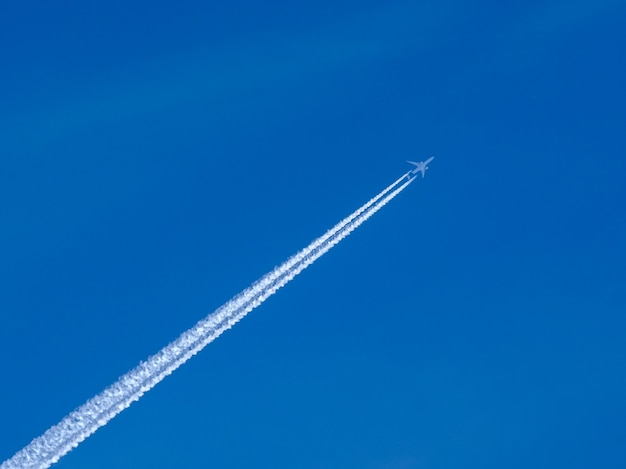 White jet passenger plane flying at high altitude in a blue clear cloudless sky