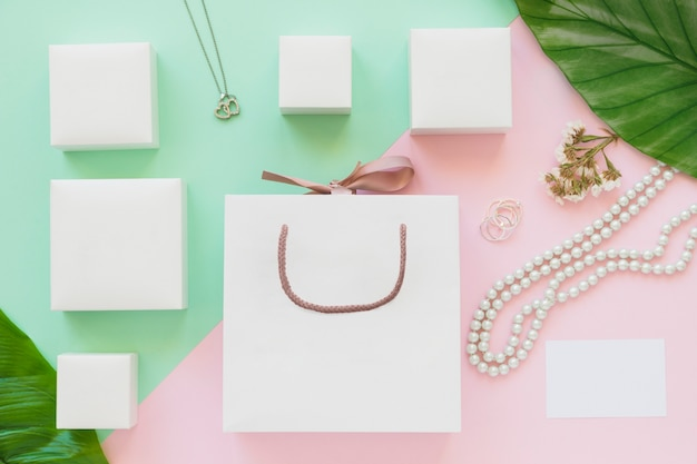 White jewel boxes and shopping bag on colored paper background