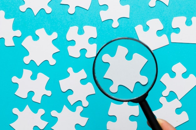 White jigsaw piece seen through magnifying glass over blue white background
