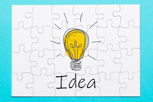 White jigsaw puzzle background with idea text and bulb drawing