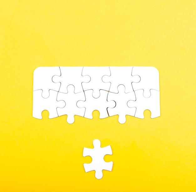 노란색 배경에 고립 된 흰색 직소 퍼즐