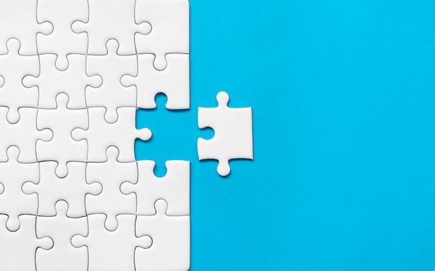 파란색 배경에 흰색 직소 퍼즐입니다. 팀 비즈니스 성공 파트너십 또는 팀워크.