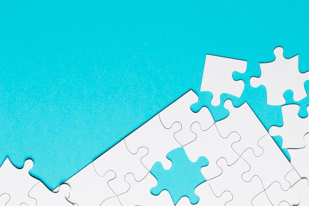 White jigsaw puzzle piece on blue backdrop