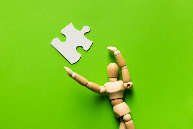 White jigsaw puzzle piece and wooden human figure over green surface