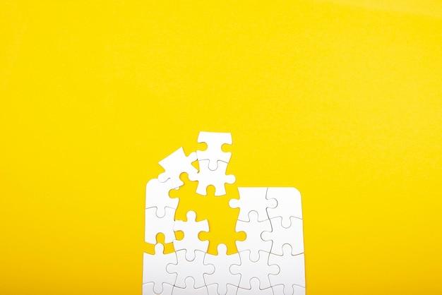노란색 배경에 고립 된 흰색 직소 퍼즐 조각