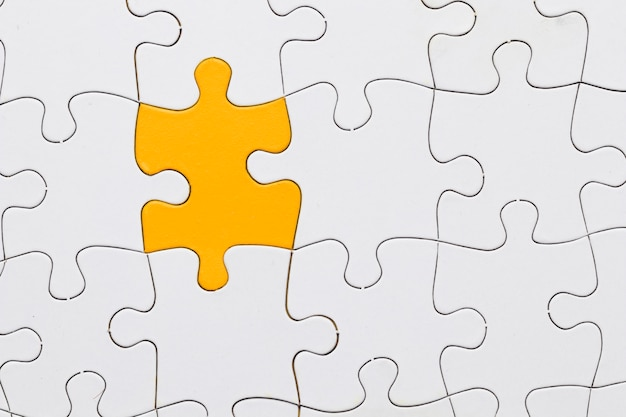 White jigsaw puzzle sheet with yellow puzzle piece in center