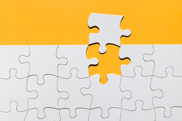 White jigsaw puzzle texture on yellow background