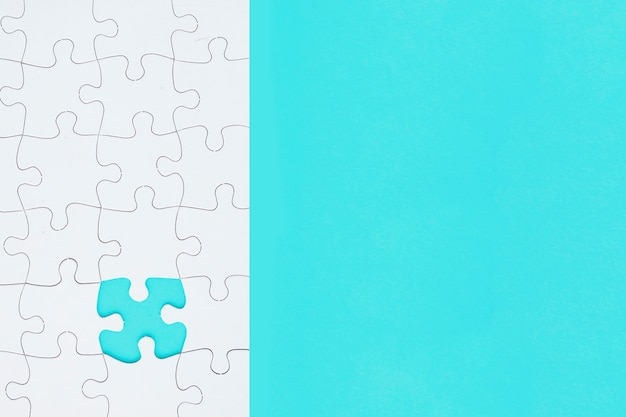 White jigsaw puzzle with missing piece on turquoise background