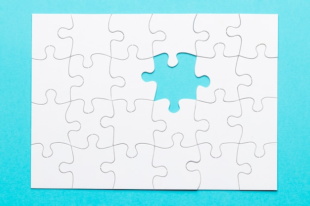 White jigsaw puzzle with one missing piece on blue backdrop