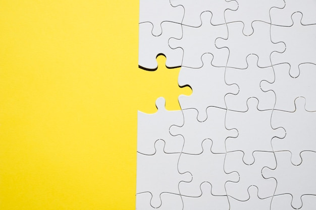 White jigsaw puzzle with one missing piece on yellow backdrop