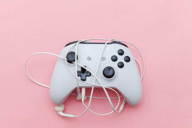White joystick and earphones on pink background.