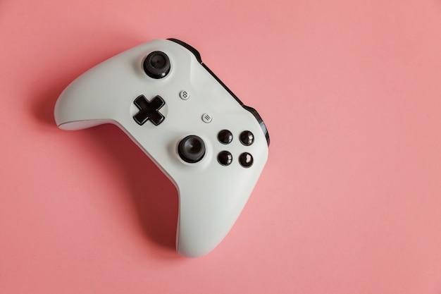 Белый джойстик-геймпад, игровая приставка на пастельно-розовом фоне